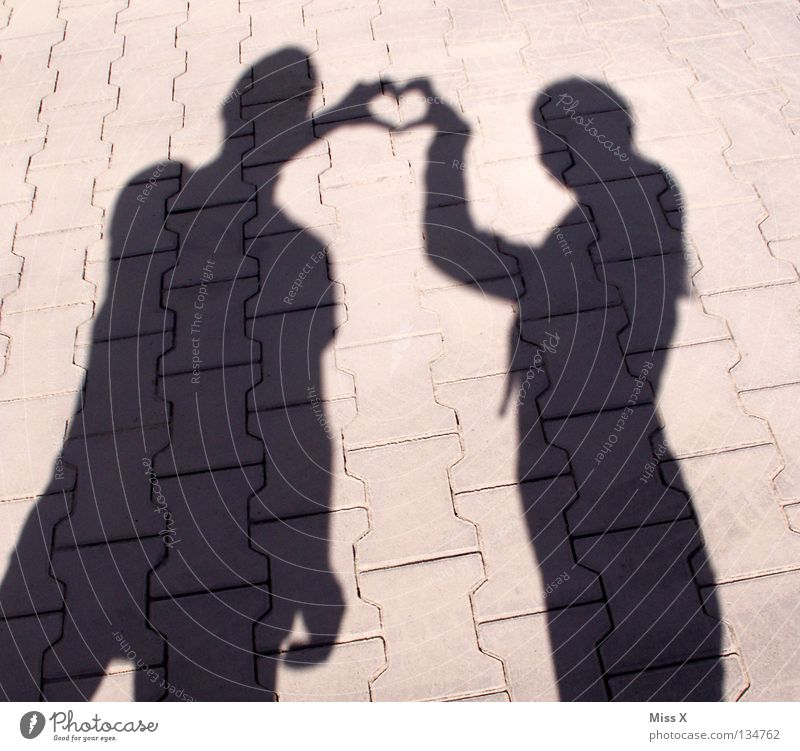 Shady sides of love Colour photo Black & white photo Exterior shot Shadow Silhouette Human being Woman Adults Friendship Hand Legs Street Stone Heart Love Gray