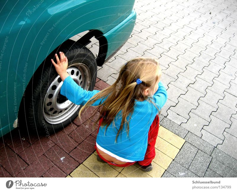 Child Green Girl Red Yellow Hair and hairstyles Stone Car Brown Touch Pants Wheel Traffic infrastructure Sweater Parking lot Tire