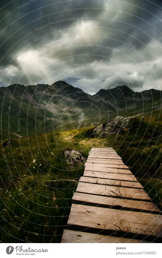 Light rays meet wooden path made of planks on alpine meadow with mountain landscape Lanes & trails Mountain Hiking Nature Landscape Sky Clouds Beam of light