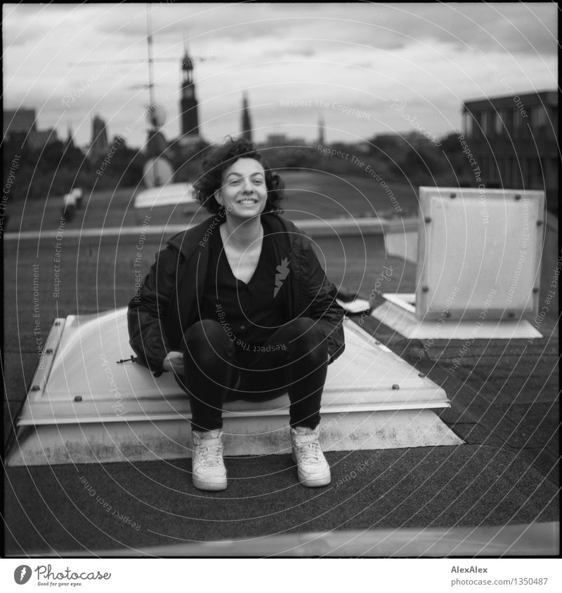 uprising Young woman Youth (Young adults) 18 - 30 years Adults Town Skyline Roof St. Michael's Church Sneakers Brunette Curl Skylight Smiling Laughter Sit