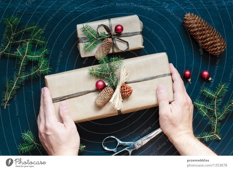 Wrapped Christmas presents on the table Scissors Hand Paper Packaging Box String Culture Tradition Guest December Gift Home Horizontal Pine Colour photo