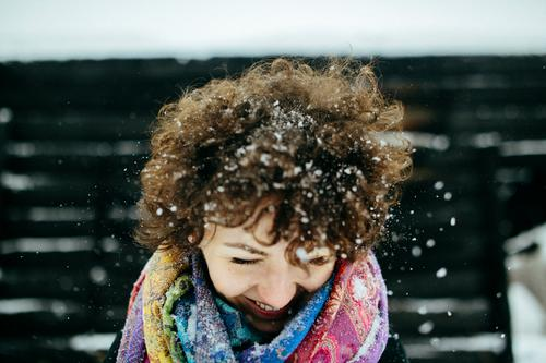 Winter fun Young woman Youth (Young adults) Adults Head Hair and hairstyles 1 Human being 18 - 30 years Wind Snow Snowfall Scarf Brunette Curl To enjoy Smiling