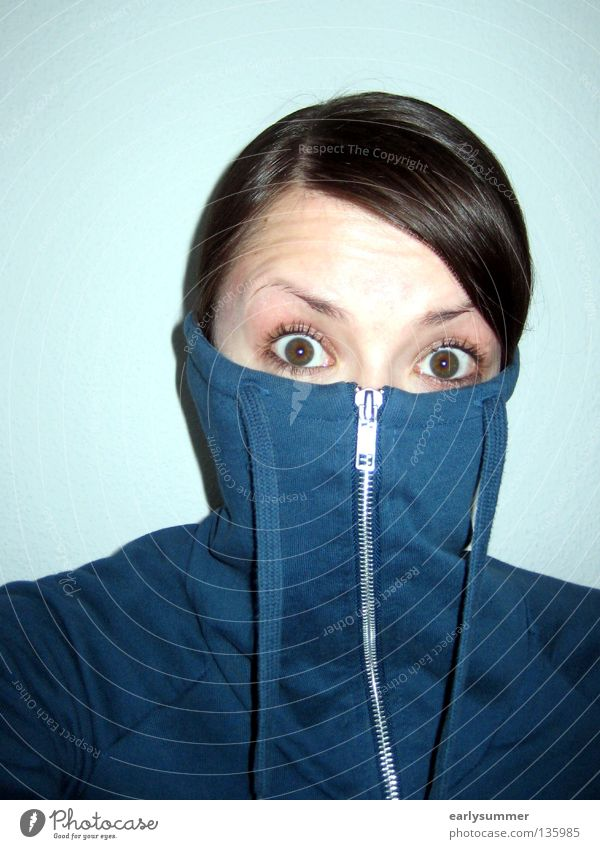 Woman hides face and looks scared Dangerous Eyebrow Frightening Scare Shock Timidity Observe Panic Fear Hooded (clothing) Roll-necked sweater Zipper Hand Wave