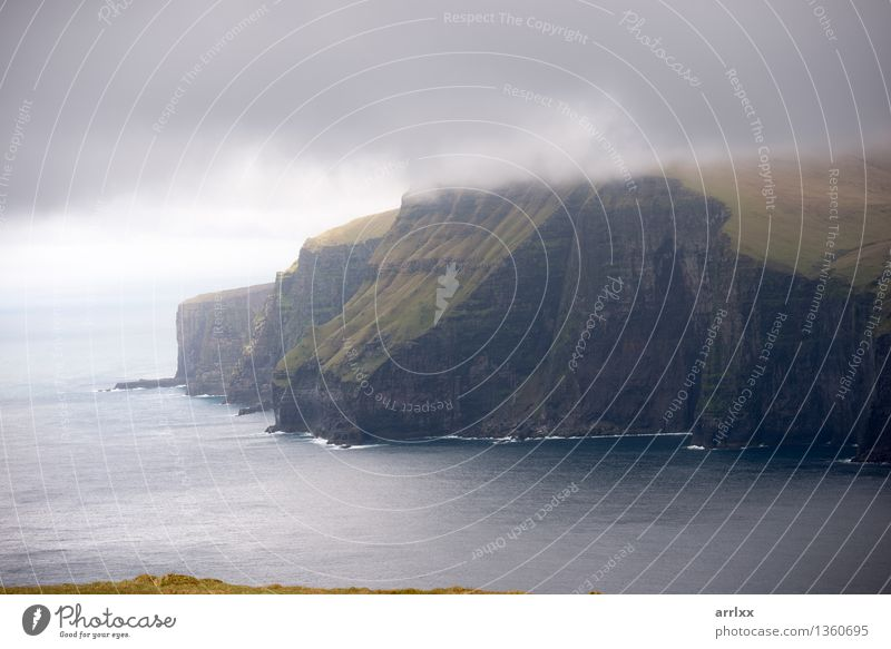 Landscape on the Faroe Islands Beautiful Ocean Mountain Environment Nature Clouds Weather Grass Meadow Rock Stone Gray Green Adventure Freedom intense Dramatic