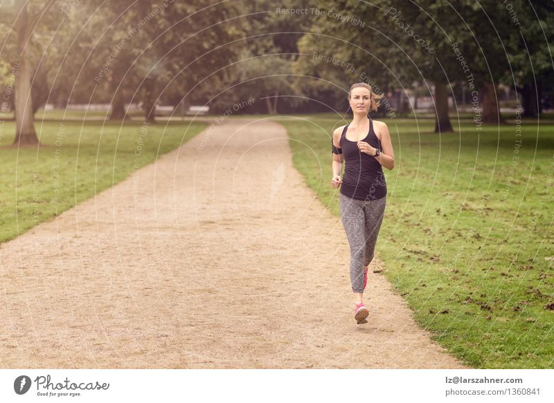 Athletic woman exercising in a park Summer Sports Jogging Woman Adults Nature Determination Action athlete athletic cardio Copy Space Practice healthy Jogger