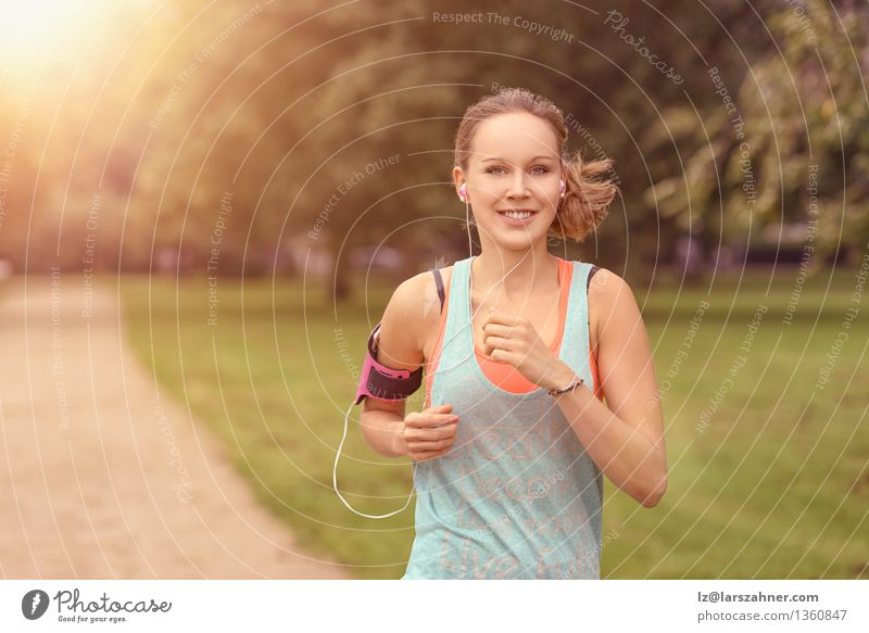 Pretty athletic woman running in a park Lifestyle Happy Summer Music Sports Jogging Woman Adults Landscape Autumn Leaf Park Street Movement Fitness Listening
