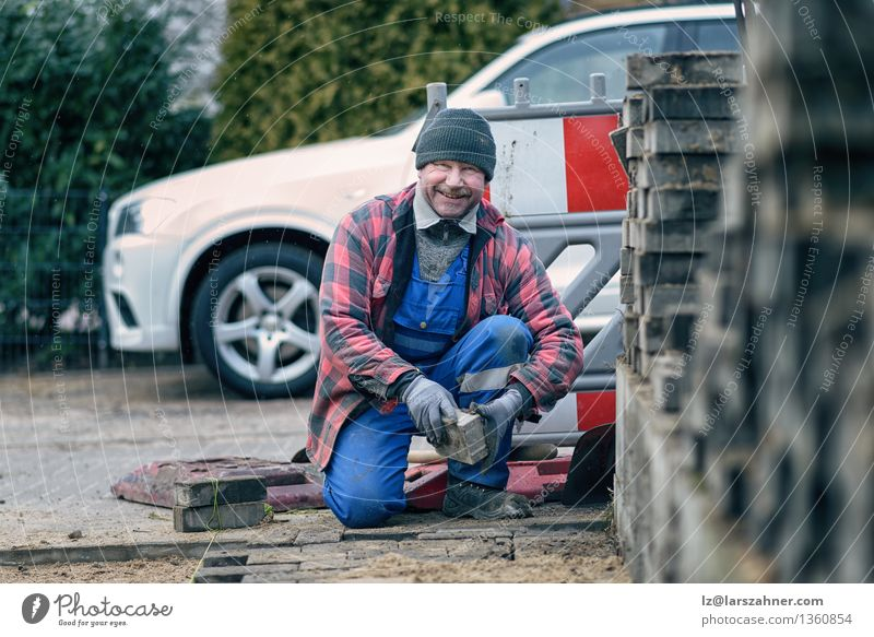 Cheerful workman in winter clothing smiling at the camera Man Winter Face Adults Street Snow Happy Work and employment Weather Smiling Friendliness Seasons Hat