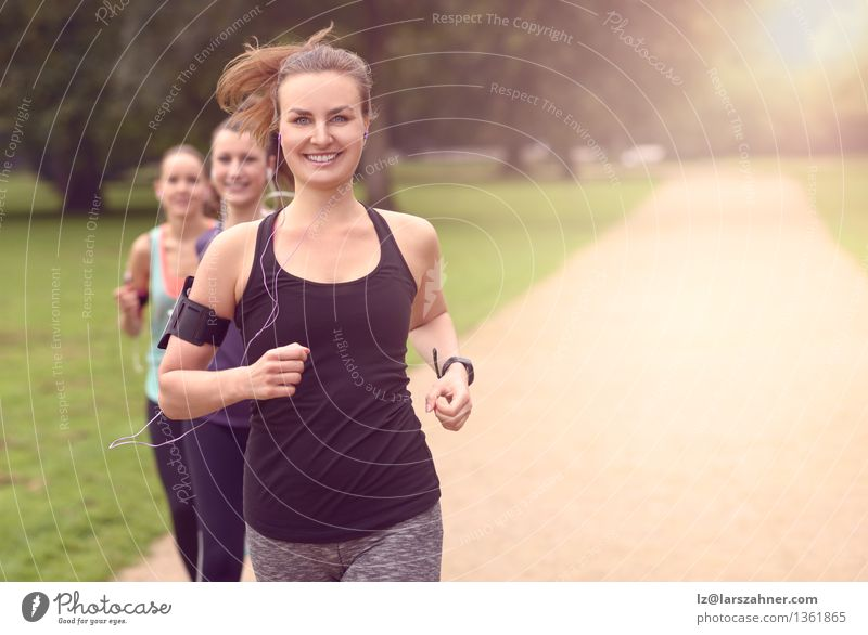 Athletic pretty young women jogging Woman Dog Summer Relaxation Adults Sports Lifestyle Group Together Friendship Park Action Copy Space Music Arm Smiling