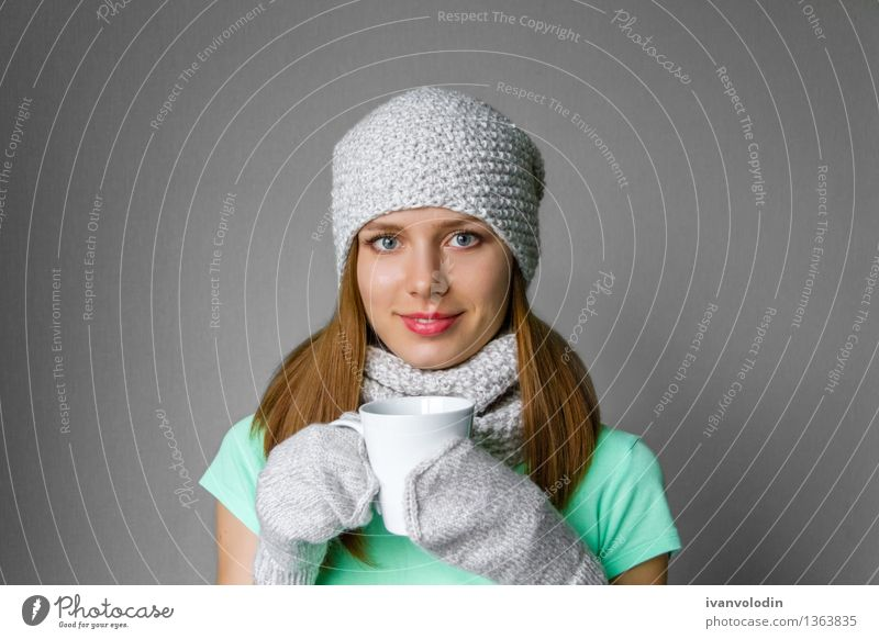 Smiling young girl in winter cap, scarf and mittens with mug Human being Woman Beautiful White Joy Girl Winter Face Adults Warmth Happy Fashion Hair Happiness