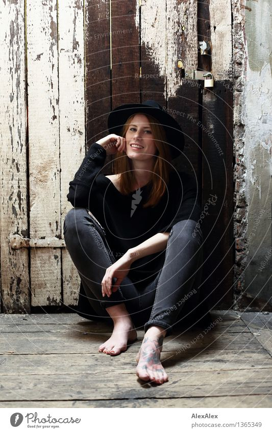 nonchalantly Lifestyle Style Beautiful Young woman Youth (Young adults) Body Feet Barefoot Model Attic Wooden door Wooden wall Jeans Hat Red-haired Long-haired