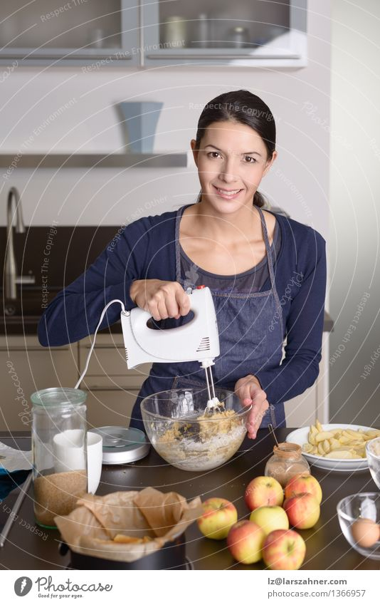 Young woman baking an apple pie in the kitchen - a Royalty Free ...