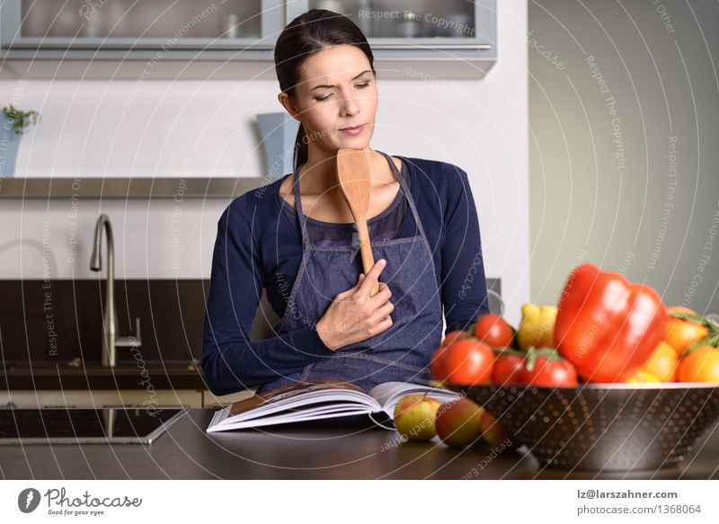 Woman Holding Ladle While Reading a cookbook Vegetable Fruit Nutrition Bowl Face Kitchen Gastronomy Adults 1 Human being 30 - 45 years Book Think Modern Natural