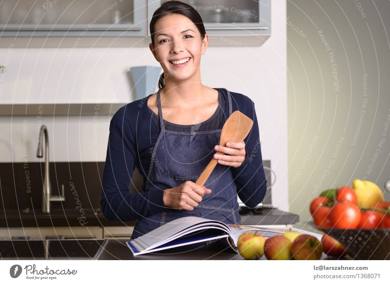 Woman Holding Ladle While Reading a cookbook Vegetable Fruit Nutrition Bowl Happy Face Kitchen Gastronomy Adults 1 Human being 30 - 45 years Book Think Smiling