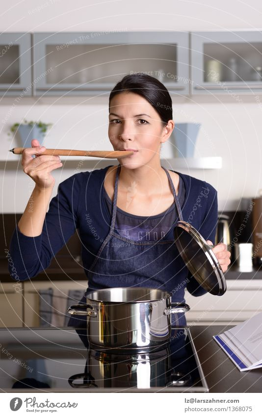 Young housewife tasting her cooking Dinner Pot Spoon Lifestyle Face Kitchen Cook Woman Adults 1 Human being 30 - 45 years Smiling Happy Testing & Control Food