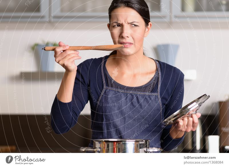 Young cook tasting her food with a grimace Dinner Pot Spoon Face Kitchen Cook Woman Adults 1 Human being 30 - 45 years Hot Anger Food attractive Cooking dislike