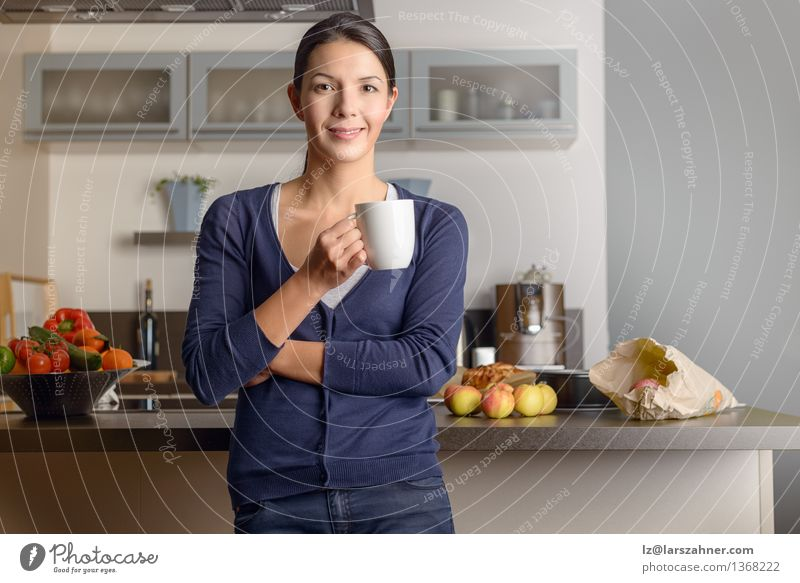 Happy contented housewife in her kitchen Human being Woman White Relaxation Calm Face Adults Happy Modern Happiness Smiling Cooking & Baking Friendliness Kitchen Coffee Vegetable
