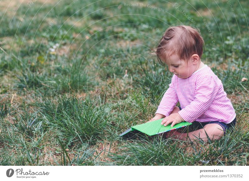 Little baby girl watching a book with pictures Lifestyle Joy Happy Beautiful Playing Child Human being Baby Toddler Girl Infancy 1 0 - 12 months Book Grass