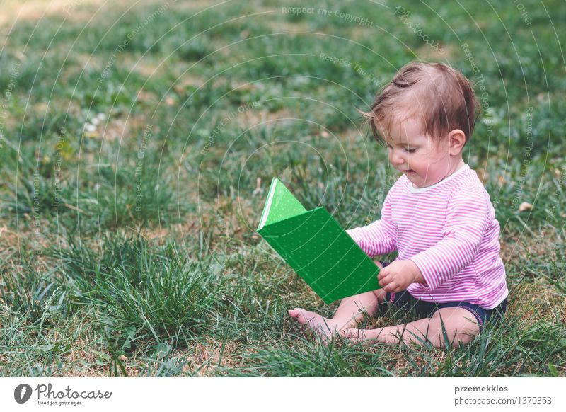Little baby girl watching a book with pictures Lifestyle Joy Happy Beautiful Child Human being Baby Toddler Girl Infancy 1 0 - 12 months Book Grass Observe