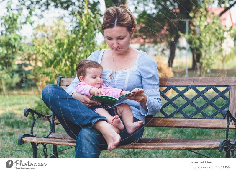 Mom reading a book her little daughter Lifestyle Joy Happy Beautiful Reading Garden Child Baby Toddler Girl Woman Adults Parents Mother Family & Relations