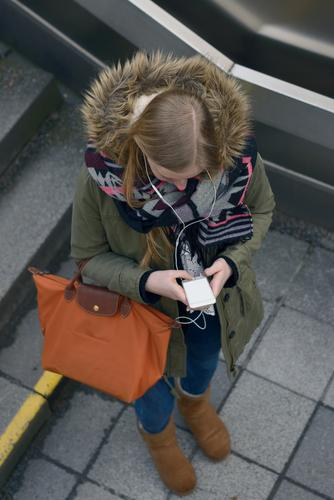 Young woman checking an sms on her mobile Reading Winter University & College student Telephone PDA Screen Technology Woman Adults 1 Human being 13 - 18 years