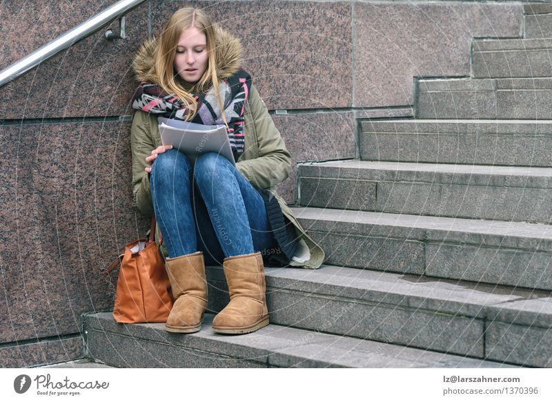 Young woman sitting reading on urban steps Human being Woman Youth (Young adults) Relaxation Girl Winter Adults Autumn Think Lifestyle School Stone Fashion