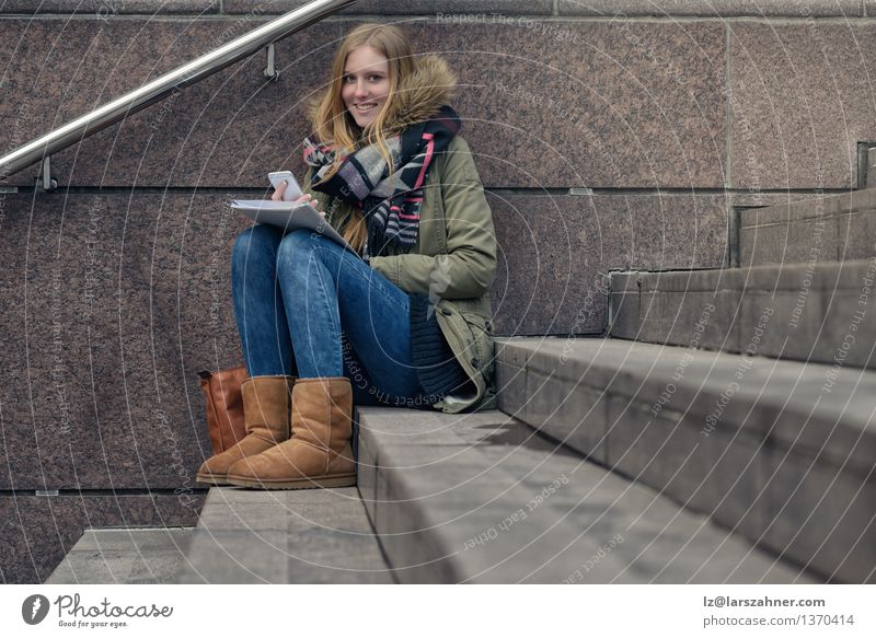 Attractive teenager sitting on steps in town Lifestyle Happy Face Reading Winter School Study Telephone PDA Girl Woman Adults 1 Human being 13 - 18 years
