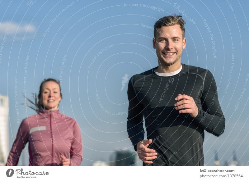 Smiling handsome man jogging with his wife Human being Woman Sky Youth (Young adults) Man Blue Relaxation 18 - 30 years Face Adults Movement Sports Happy