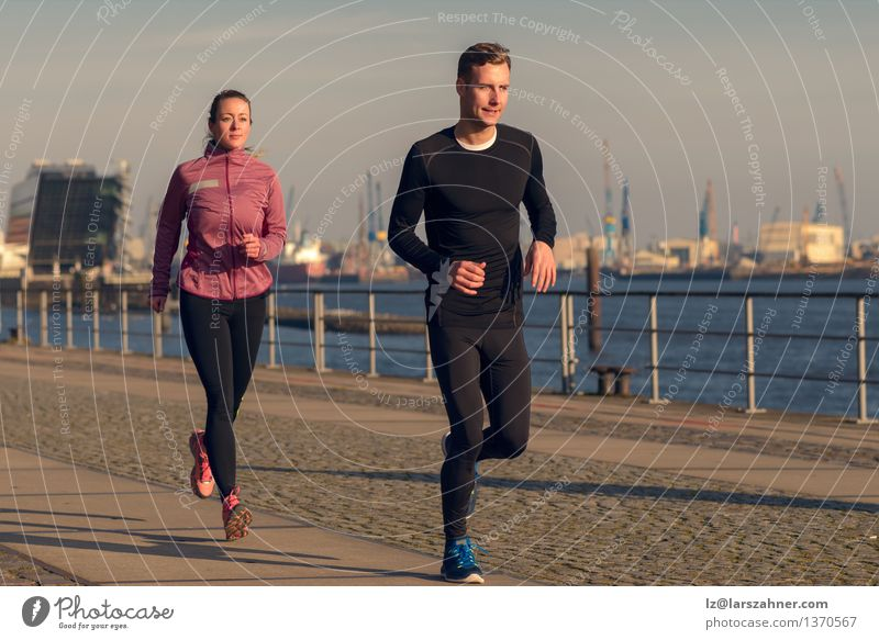 Young couple running on a seafront promenade Human being Woman Youth (Young adults) Man Relaxation 18 - 30 years Face Adults Sports Lifestyle Couple Action