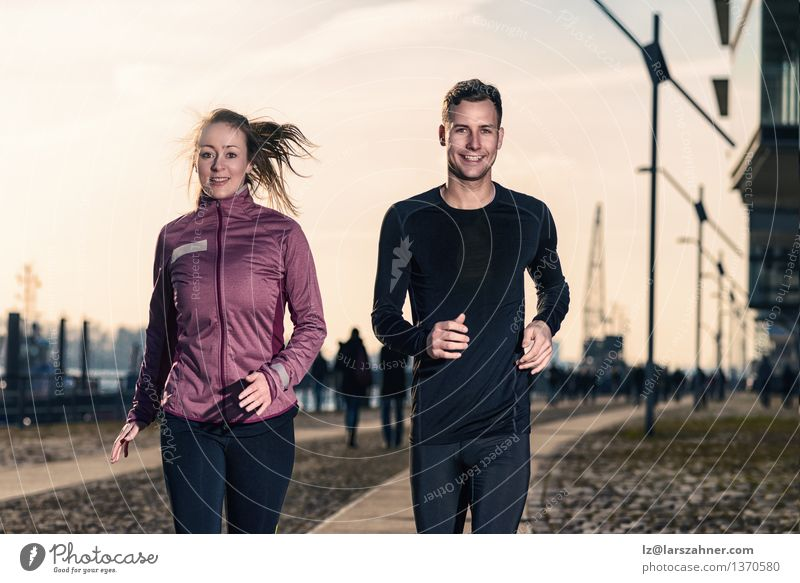 Active young couple jogging in an urban street Human being Woman Youth (Young adults) Man City 18 - 30 years Face Adults Street Sports Happy Lifestyle Couple Together Action Success