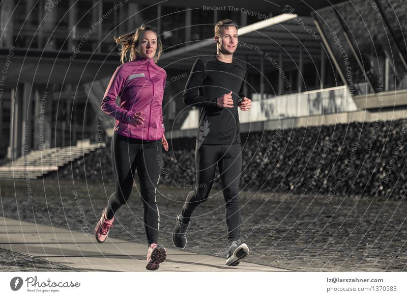 Active young couple jogging in an urban street Lifestyle Face Sports Success Jogging Woman Adults Man Couple 2 Human being 18 - 30 years Youth (Young adults)