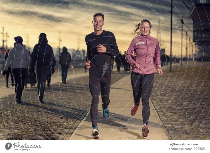Active young couple jogging on a harbor promenade Human being Woman Youth (Young adults) Man 18 - 30 years Face Adults Street Sports Lifestyle Couple Together Action Success Energy Fitness
