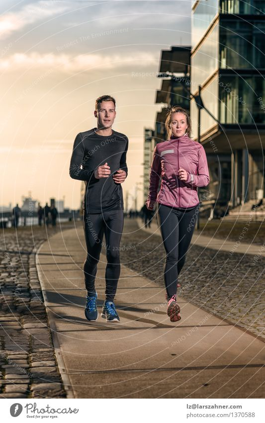 Active young couple jogging on a harbor promenade Human being Woman Youth (Young adults) Man 18 - 30 years Face Adults Street Sports Lifestyle Couple Together