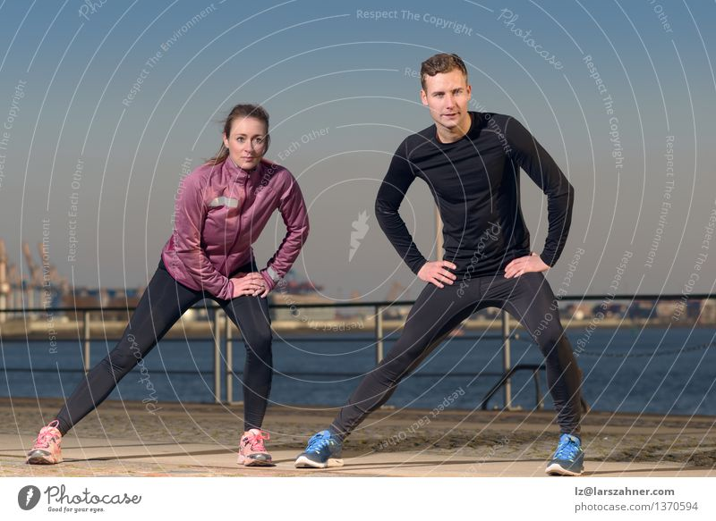 Young couple exercising at the waterfront Lifestyle Body Wellness Leisure and hobbies Sports Jogging Woman Adults Man Friendship Couple 2 Human being Autumn