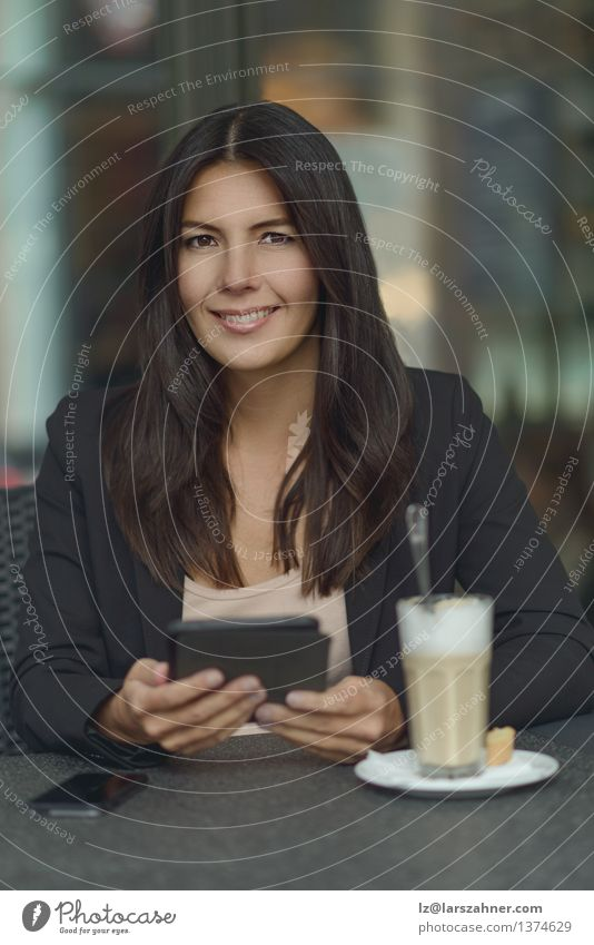 Smiling woman in coffee shop Beverage Coffee Lifestyle Relaxation Reading Table Business Telephone Woman Adults Suit Brunette Sit To call someone (telephone)