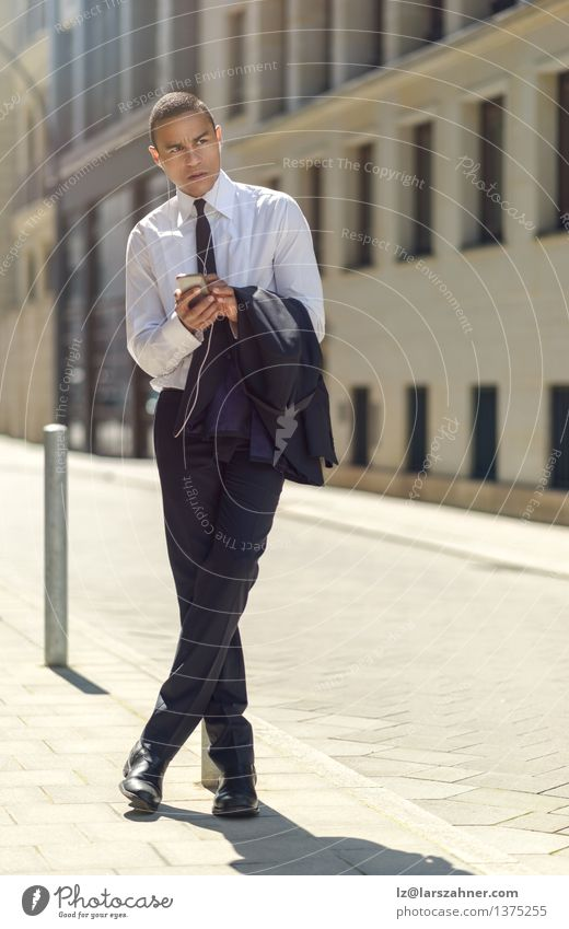 Businessman sitting on a bollard reading an sms Man Summer Adults Modern Copy Space Sit Technology Reading Telephone Information Sidewalk Suit Headphones