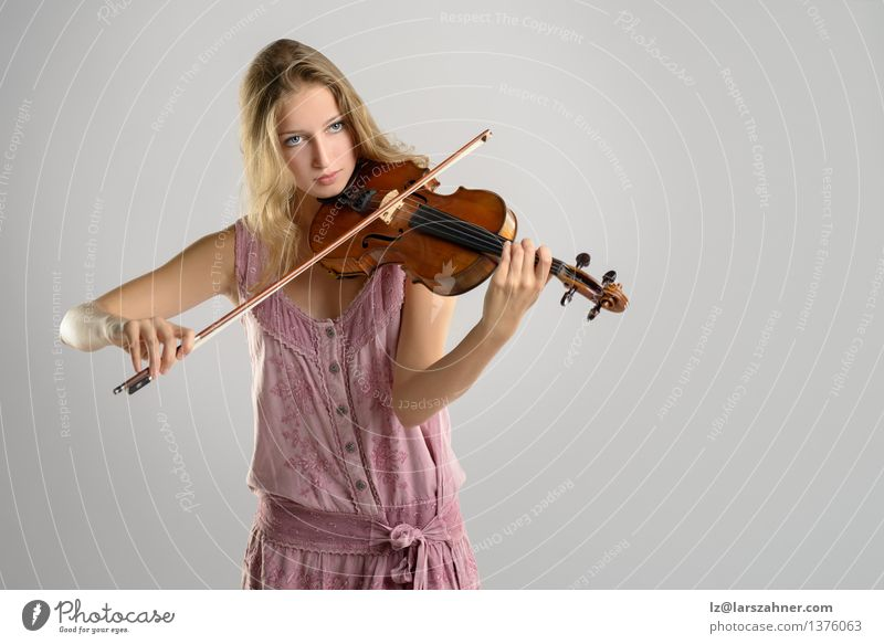 Pretty young violinist playing the violin Playing Music Academic studies Girl Woman Adults Youth (Young adults) Art Culture Concert Musician Violin Stand artist