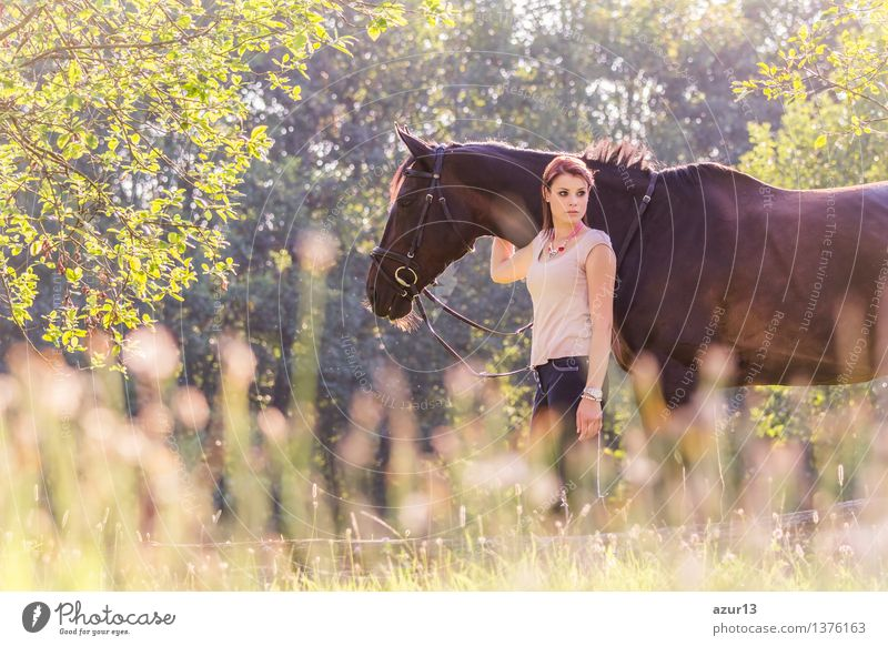 Beautiful young equestrian woman with horse in summer sun nature. Portrait of a teenager horsewoman holding her best animal friend in a lovely sunny outdoor scene. Landscape format with copyspace.