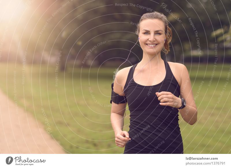 Pretty Woman Jogging at the Park with Headphones Lifestyle Happy Summer Music Sports Adults Landscape Autumn Leaf Street Movement Fitness Listening Smiling