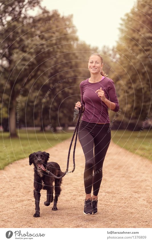 Healthy Woman Jogging in the Park with her Dog Woman Dog Summer Relaxation Animal Adults Lanes & trails Sports Lifestyle Together Friendship Park Action Smiling Fitness Pet