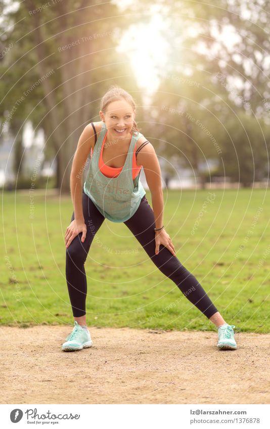 Athletic young woman doing stretching exercises Lifestyle Happy Body Wellness Summer Woman Adults Nature Park Fitness Smiling Happiness Muscular athlete