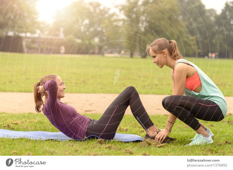 Athletic woman doing curl up exercises Lifestyle Happy Body Sports Fitness Sports Training Sportsperson Woman Adults Friendship Arm Feet Grass Park Smiling