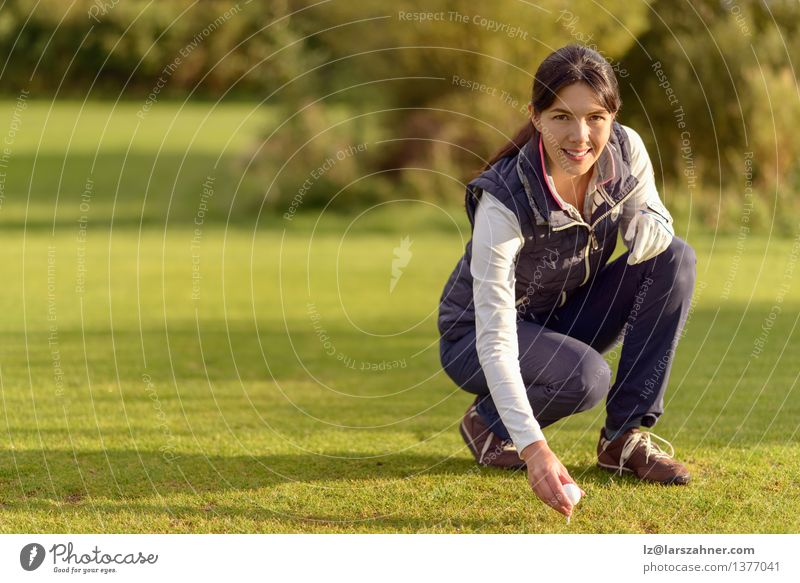 Smiling attractive young female golfer bending down Face Relaxation Leisure and hobbies Playing Sports Golf Woman Adults Nature Brunette Green Fairway ball