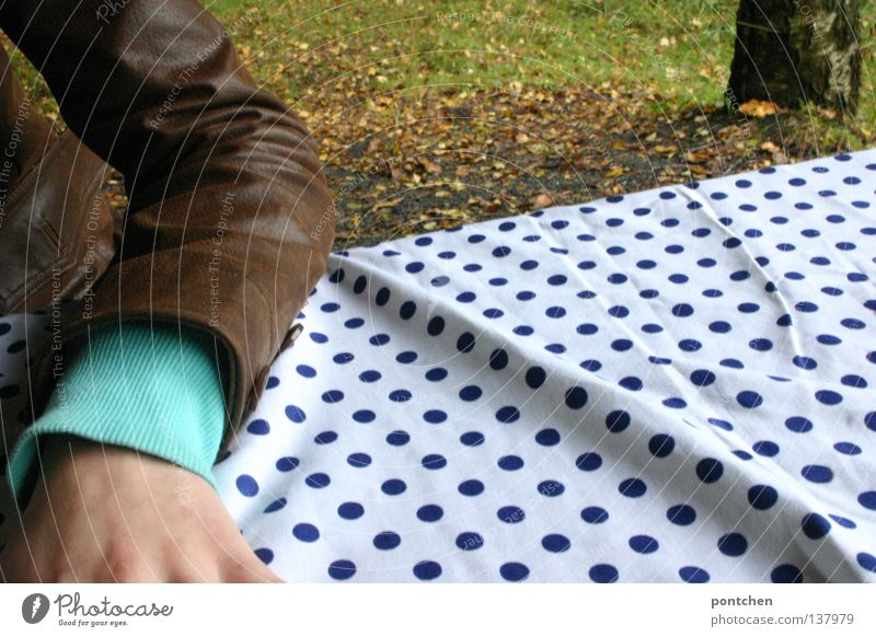 Forearm with cut arm lying on a dotted tablecloth on a table in the woods. Leather jacket. Picnic Relaxation Table Human being by hand Nature Autumn flaked