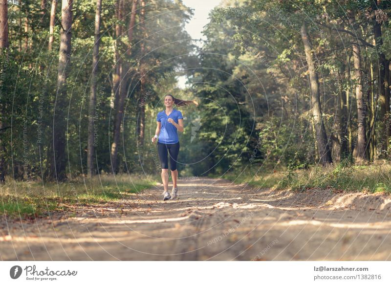 Athletic woman out jogging in a forest Lifestyle Body Sports Jogging Girl Woman Adults 1 Human being 18 - 30 years Youth (Young adults) Nature Landscape Sand
