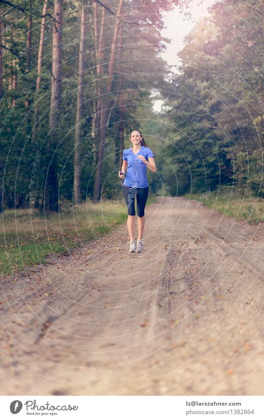 Athletic woman out jogging in a forest Human being Woman Nature Youth (Young adults) Loneliness Landscape Girl 18 - 30 years Forest Adults Sports Lifestyle Sand Body Action Music