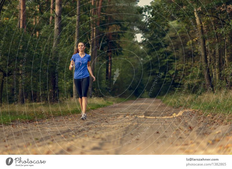 Athletic woman out jogging in a forest Lifestyle Body Music Sports Jogging Technology Girl Woman Adults 1 Human being 13 - 18 years Youth (Young adults) Nature