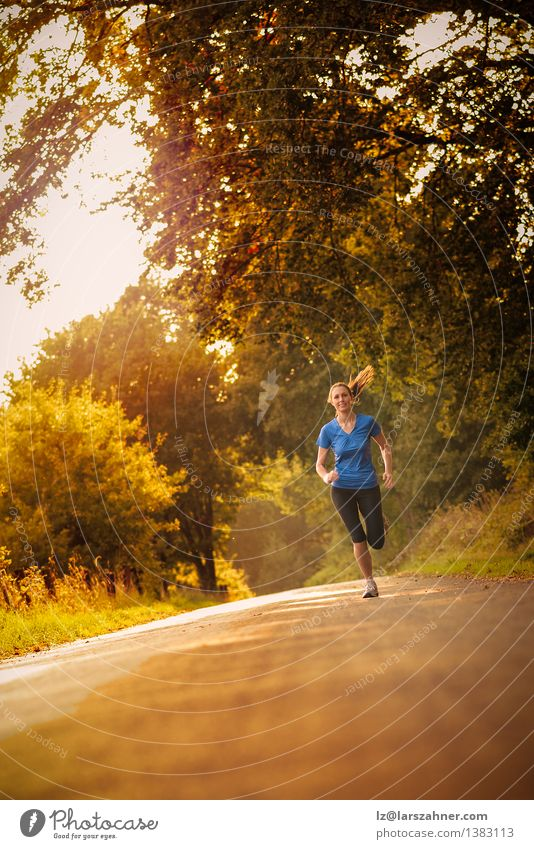 Sporty woman running on a country road Human being Woman Youth (Young adults) Colour Tree Landscape Leaf Adults Street Autumn Movement Sports Happy Park Fresh