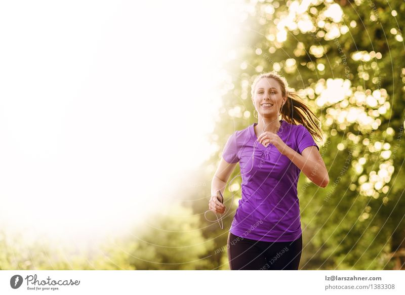 Woman listening to music while jogging Human being Youth (Young adults) Colour Summer Tree Landscape Leaf Adults Street Autumn Movement Sports Happy Lifestyle