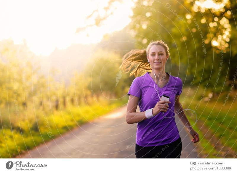 Woman listening to music while jogging on a street Colour Summer Tree Landscape Leaf Adults Street Autumn Movement Sports Happy Lifestyle Park Fresh Action