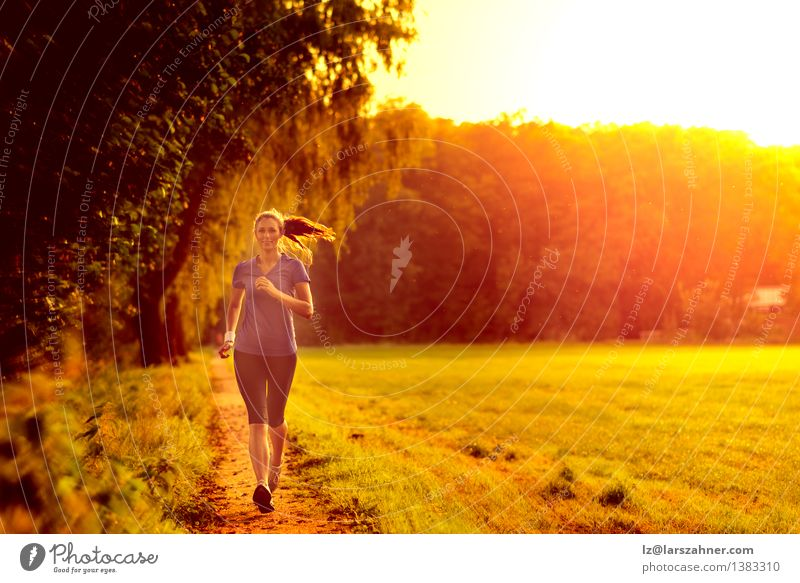 Young woman jogging along a country track Woman Green Summer Loneliness Leaf Face Adults Grass Lanes & trails Sports Lifestyle Action Energy Fitness